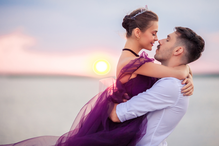 Young romantic couple relaxing-on-the-beach-watching